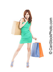 full length of happy young woman with shopping bag