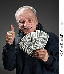 Happy elderly man showing fan of money and sign OK with...