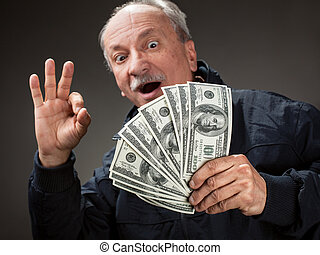Happy elderly man showing fan of money