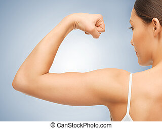 sporty woman flexing her biceps - closeup picture of sporty...