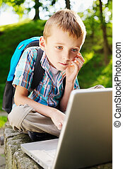 Boy with notebook in the park