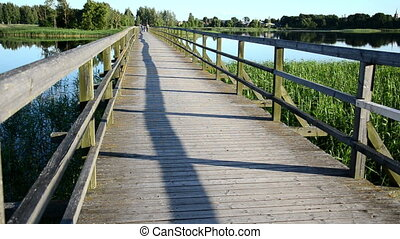 wooden bridge people - wooden bridge with railings through...