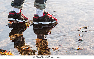 stepping stone, risk taking - close up of young boy's shoes...