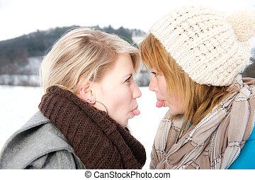 zwei junge Frauen strecken sich die Zungen raus
