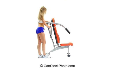 Athletic young woman on hydraulic exerciser. White...