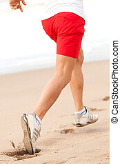 young sporty man legs running on the beach