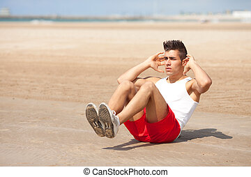 Young strong man on abs work out outdoors