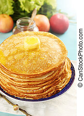 melted butter on pancakes - pile of thin pancakes on a plate