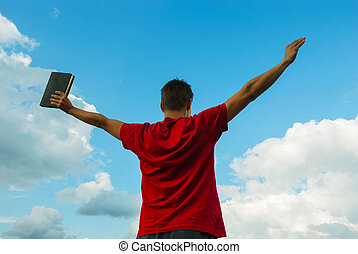 Young man staying with raised hands against blue sky