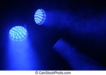three spotlights shine with blue light in the dark