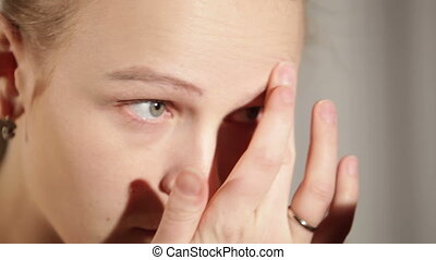 Young woman is putting cosmetic cream on her face.