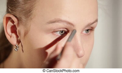 Young woman shaping her eyebrows.