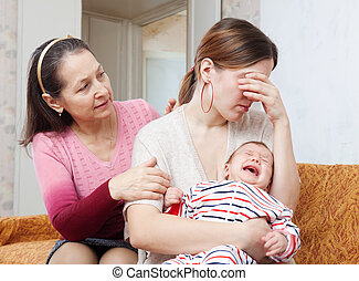 Mature woman gives solace to crying adult daughter with baby...