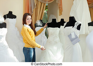 bride chooses wedding outfit in bridal boutique - Smiling...