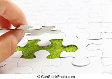 Hand embed missing puzzle piece into place, green space...