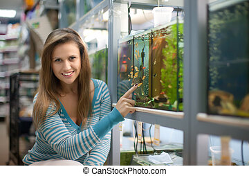 Woman chooses aquarium for fishes in pet-shop