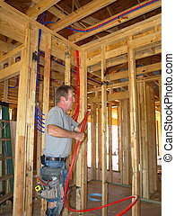 Plumber bending red pex plumbing pipe