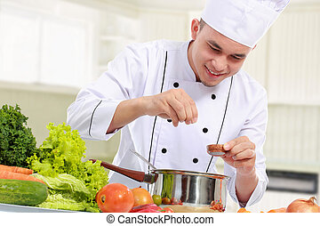 male chef while cooking - happy smiling male chef put some...