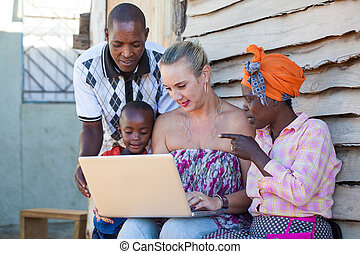 Showing pictures - A caucasion woman are showing to African...