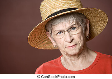Senior woman in a straw hat - Senior woman in a red shirt...