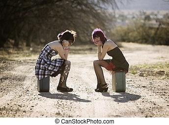 Girsl waiting on a rural road