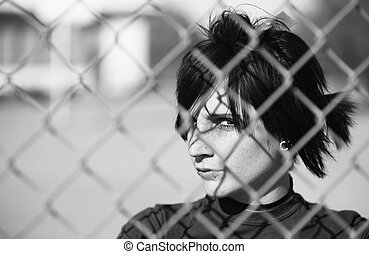 Punk Girl Behind Chain Link - Young Punk Girl Being Shadowed...
