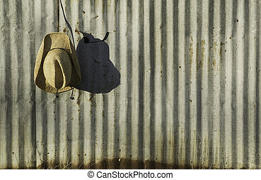 Cowboy hat against corrugated metal. - Straw cowboy hat...