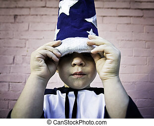 Boy looking out from a wizard hat - Young boy lifts the brim...