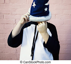 Little boy in a sorcerer hat picks his nose - Young boy in a...