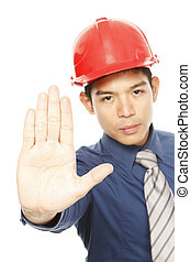 Stop Right There - Man wearing a hard hat signaling a stop...