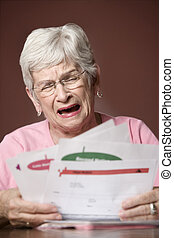 Senior woman with bills and notices - Upset senior woman...