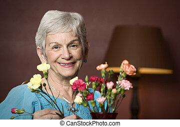 Woman with flowers - Senior woman at home with colorful...