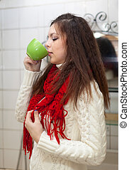 Colds woman with cup of medicine gargling at bathroom
