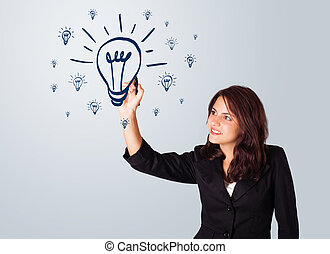 Woman drawing light bulb on whiteboard - Young woman drawing...