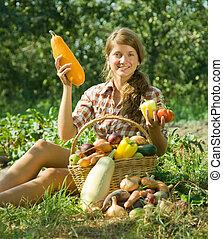 girl sitting near basket of harvest