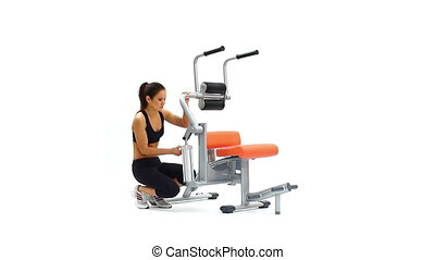 Slim woman on hydraulic exerciser. White background