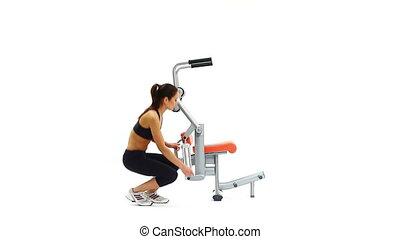 Slim young woman on hydraulic exerciser. White background