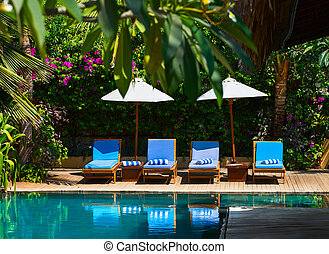 Swimming pool in tropical resort - Beach chairs near...