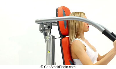 Blonde woman on hydraulic exerciser. White background