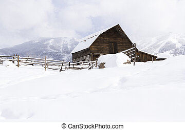 Old barn - Aged barn on snowy hillside with ski lifts and...