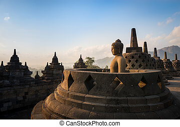Buddha in Borobudur Temple at sunrise. Indonesia. - Buddha...