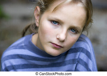 Sad little girl is looking with serious face at camera.