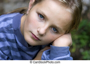 Sad little girl is looking with serious face at camera