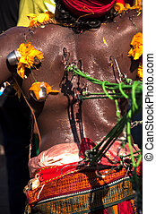 thaipusam devotee carries cavadi in Batu Caves in Malaysia