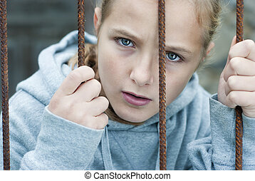 Child abuse - Sad lonely child is behind grid