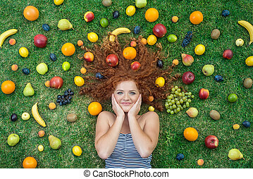 Girl with fruit lying on the grass
