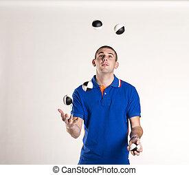 juggler - Young man juggling with several balls at once