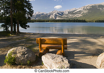 Pine Bench at Lake - Pine bench at the shore of a lake in...