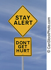 Stay Alert! - Road sign with a safety reminder against a...