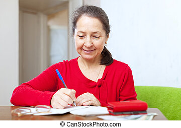 woman is calculated the family budget - serious woman is...
